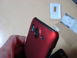 Front top angled view of phone with red case in hand