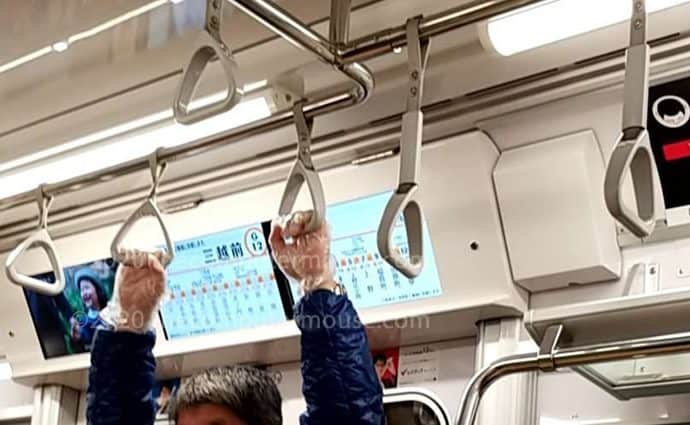 Guy wearing plastic gloves to avoid infection, on the train in Japan.